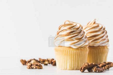 close up view of sweet cupcakes with hazelnuts isolated on white