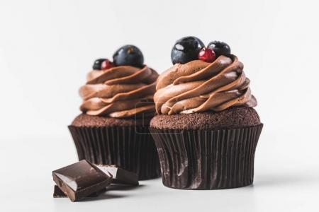 Photo pour Bouchent la vue des petits gâteaux au chocolat avec crème, des raisins, des baies et des morceaux de chocolat isolé sur blanc - image libre de droit