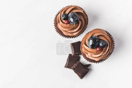 Photo for Top view of chocolate cupcakes with cream, grape, berries and pieces of chocolate isolated on white - Royalty Free Image