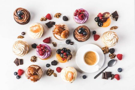 flat lay with arrangement of sweet cupcakes, teaspoon and cup of coffee isolated on white