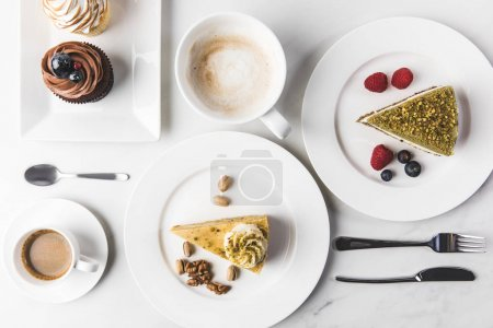 top view of arrangement of pieces of various cakes on plates, cups of coffee and cupcakes isolated on white