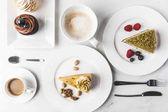 """Постер, картина, фотообои """"вид сверху расположения частей различных тортов на тарелки, чашки кофе и кексы, изолированные на белом фоне"""""""