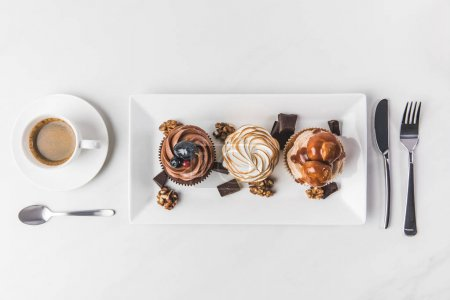 Photo for Top view of various cupcakes on plate, cup of coffee and cutlery isolated on white - Royalty Free Image