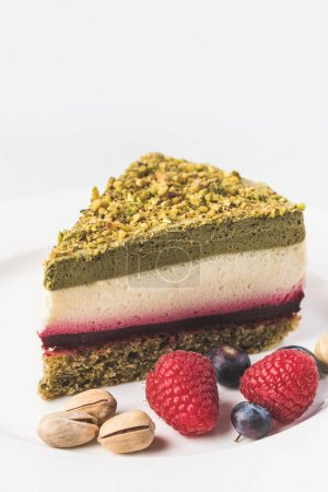 Photo for Close up view of sweet cake with pistachios and berries on plate isolated on white - Royalty Free Image