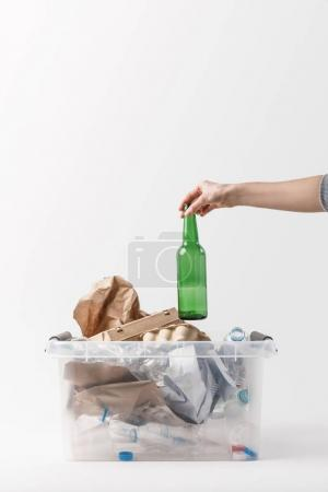 cropped shot of woman putting glass bottle into container with plastic bottles, recycle concept
