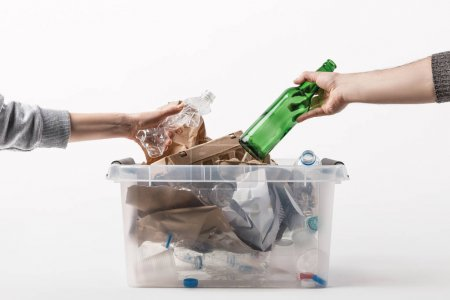 cropped shot of people putting trash into plastic container isolated on white, recycling concept
