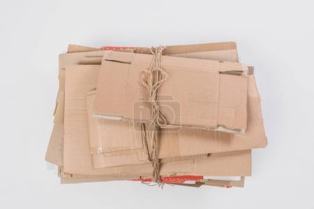 top view of pile of folded cardboard boxes isolated on grey, recycle concept