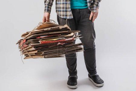 Photo pour Recadrée tir d'homme tenant des tas de boîtes de carton pliées isolé sur fond gris, concept de recyclage - image libre de droit