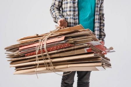 cropped shot of man holding pile of folded cardboard boxes isolated on grey, recycling concept