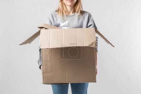 partial view of woman holding cardboard box with garbage in hands, recycle concept