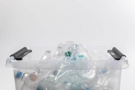 close up view of container with plastic bottles isolated on grey, recycling concept