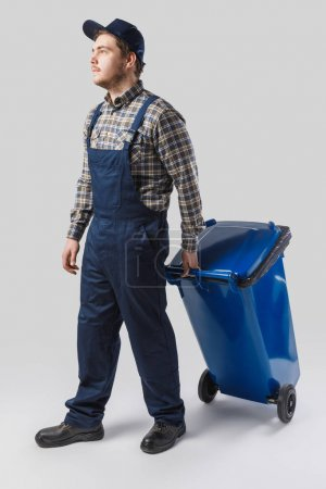 young cleaner in uniform with trash bin isolated on grey