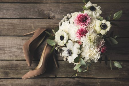 Photo for Flat lay with bridal shoes and beautiful bouquet on wooden tabletop - Royalty Free Image