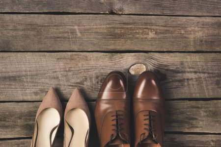 top view of bridal and grooms pairs of shoes on wooden surface