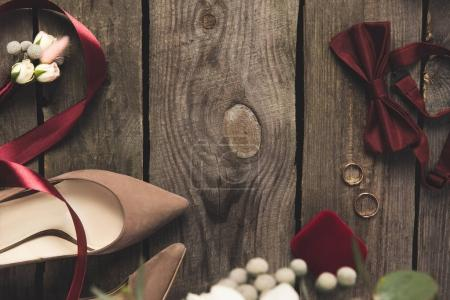 flat lay with bridal  shoes, bow tie, wedding rings on wooden surface