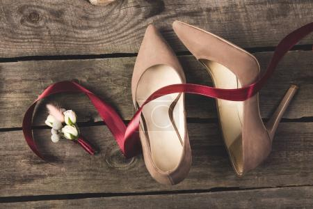 top view of beautiful bridal shoes and corsage on wooden tabletop