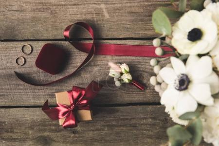 Photo for Flat lay with wedding rings, jewelry box, bridal bouquet and corsage on wooden tabletop - Royalty Free Image