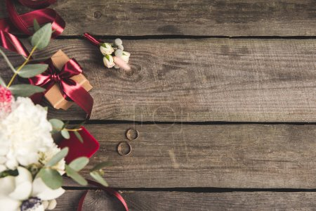 flat lay with wedding rings, jewelry box, bridal bouquet and corsage on wooden tabletop
