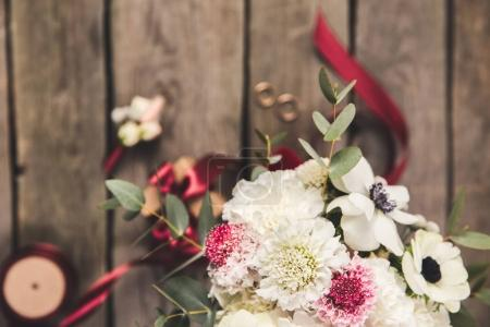 selective focus of beautiful bridal bouquet, wedding rings and ribbons on wooden surface