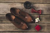 flat lay with grooms shoes and accessories on wooden surface