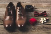 close up view of arranged grooms shoes and accessories on wooden surface