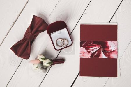 flat lay with invitation, buttonhole, bow tie and jewelry box on wooden surface