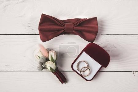 flat lay with buttonhole, bow tie and jewelry box on wooden surface