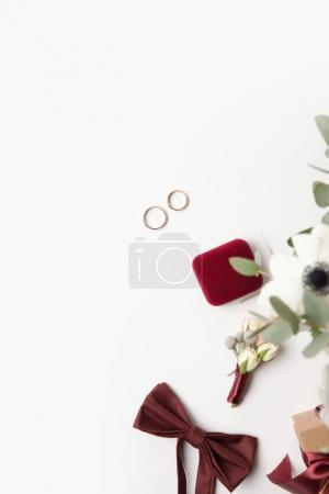 flat lay with wedding rings, buttonhole, bow tie and jewelry box isolated on white