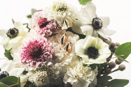 Photo for Close up view of wedding rings in bridal bouquet isolated on white - Royalty Free Image