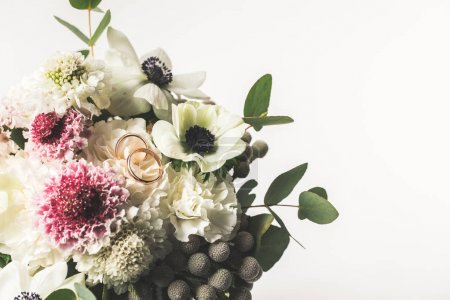 close up view of wedding rings in bridal bouquet isolated on grey