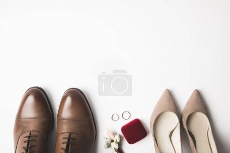 top view of pairs of bridal and grooms shoes, corsage, jewelry box and wedding rings isolated on white