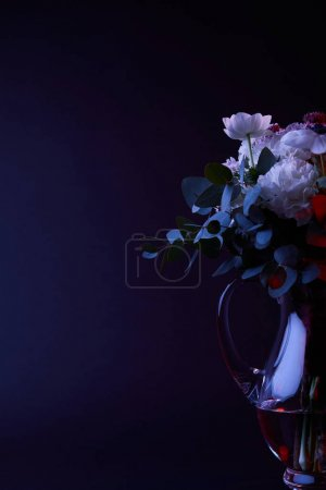 bouquet of different flowers in glass carafe on dark