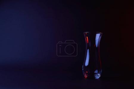 empty glass vase with reflection on dark surface