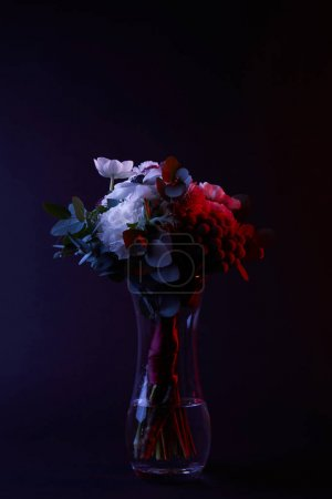 bouquet of different flowers in glass vase with red light on dark