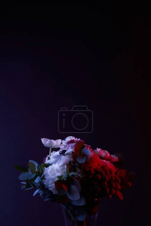 bouquet of different white flowers with red light on dark