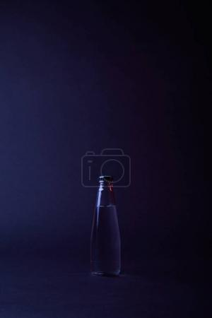 closed bottle of water on dark surface