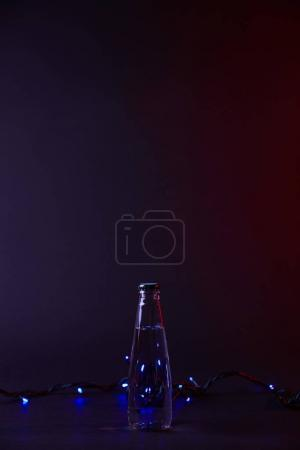 closed bottle of water and blue garland on dark surface