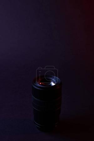 one photographic objective on dark surface