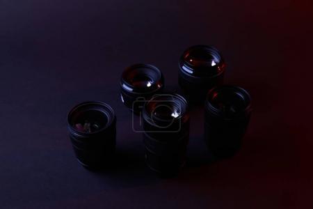 reflecting camera lenses on dark surface
