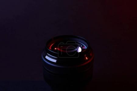 reflecting camera lens on dark surface