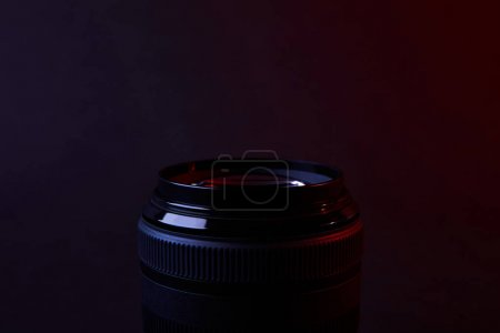one camera lens on dark surface
