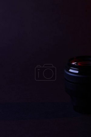 single camera lens with reflection on dark