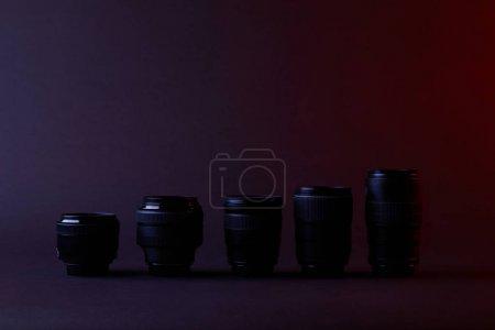 different camera lenses on dark surface
