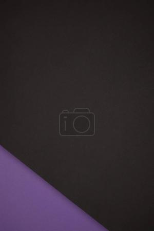 dark abstract background made from black and purple colored paper