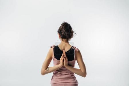 back of woman practicing yoga with namaste behind the back isolated on white