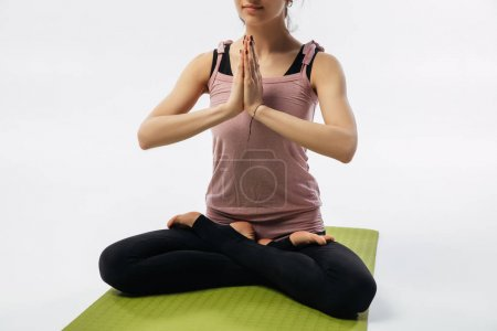 cropped image of woman practicing yoga and sitting in padmasana