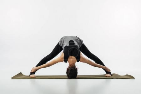 woman practicing yoga and doing wide legged forward fold