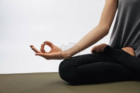 cropped image of woman meditating in yoga lotus pose isolated on white