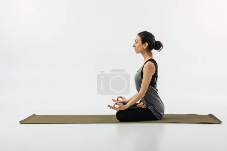 side view of woman meditating in yoga lotus pose isolated on white