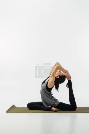 woman practicing yoga and doing king pigeon isolated on white